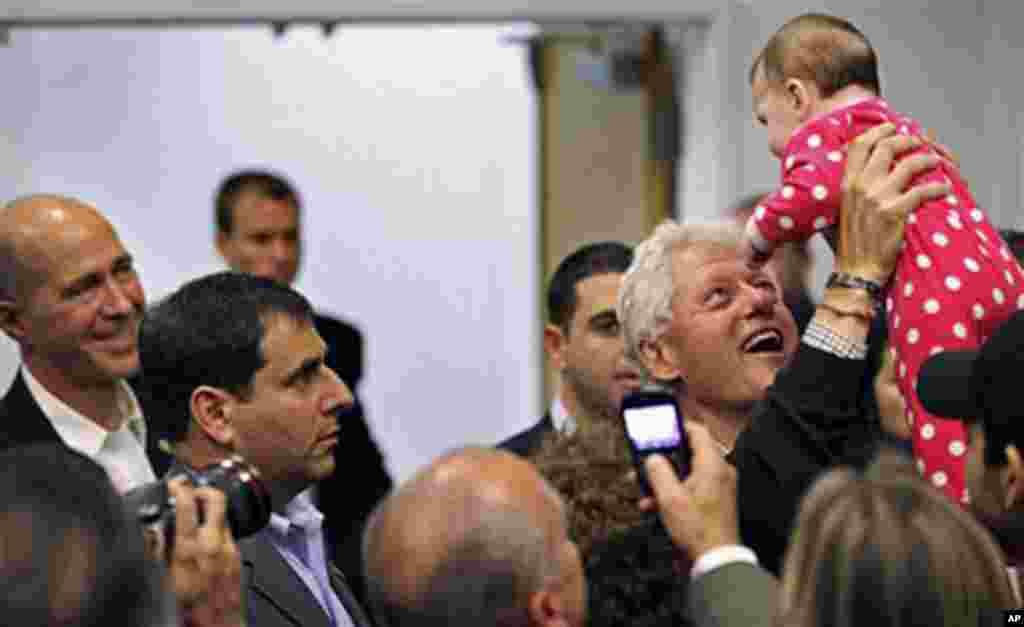 Rais wa zamani wa Marekani Bill Clinton akimbeba mtoto akiwa katika kapeni huko Washingtonville, N.Y.