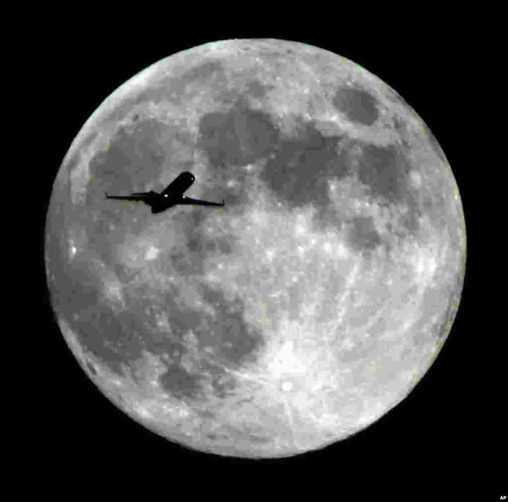 An airliner approaching Los Angeles International Airport crosses the Harvest Moon as seen from Monterey Park, California, USA, Sept 18, 2013.