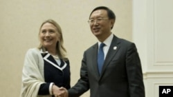 U.S. Secretary of State Hillary Rodham Clinton, left, and Chinese Foreign Minister Yang Jiechi pose for photos before their meeting on the sideline of the ASEAN regional forum in Phnom Penh, July 12, 2012.