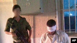A handout picture from Israeli human rights organization Breaking the Silence, 18 Aug 2010, shows an undated photograph of an Israeli soldier posing near a handcuffed and blindfolded Palestinian detainee at an undisclosed location