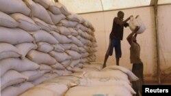 FILE - Men transport humanitarian food aid onto trucks in Sevare, Mali, Feb. 4, 2013.