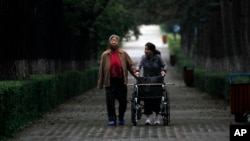 FILE - An elderly Chinese woman accompanied by her caregiver walks down a tree lined lane in Changchun in northeastern China's Jilin province, Aug. 27, 2010.