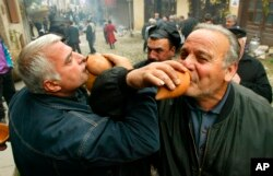 FILE - Georgian men drink wine during a wine festival in Signakhi, in the Kakheti region, Georgia, Saturday, Oct. 28, 2006.