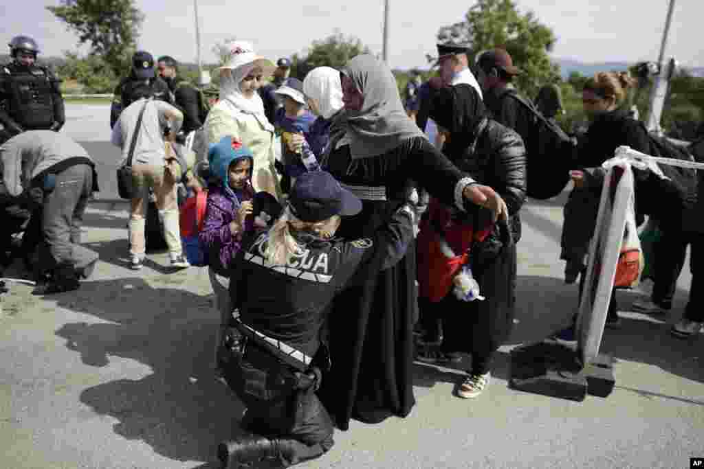 A police officer searches refugees after they entered Slovenia, as they wait for a bus transport at the border station in Obretzje.