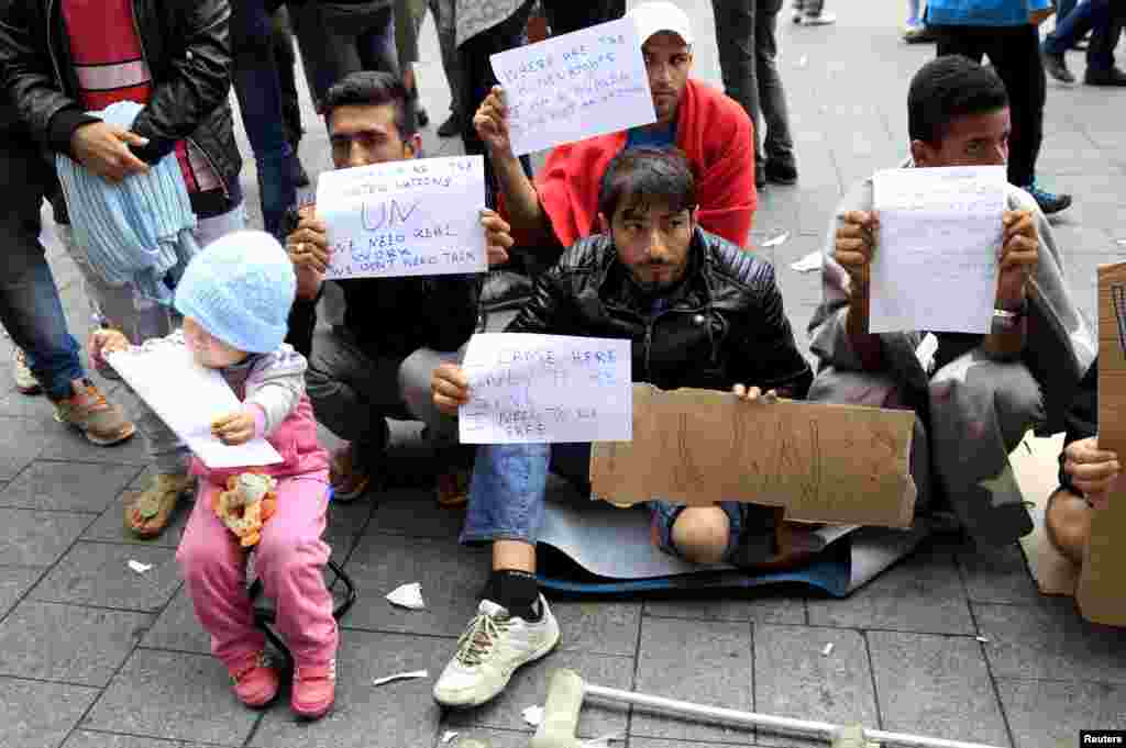 Migrants hold signs in front of Keleti railway station in Budapest, Hungary, Sept. 4, 2015.