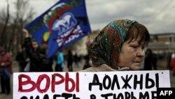 Một người trong nhóm đối lập biểu tình cầm biểu ngữ với hàng chữ 'Những tên trộm nên ngồi tù' cùng với những bức ảnh của Thủ tướng Putin