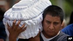 지난 3일 콰테말라 시티 외곽에서 발생한 산사태로 수백명이 사망한 가운데, 한 남성이 산사태로 사망한 5살 난 조카의 관을 운반하고 있다.