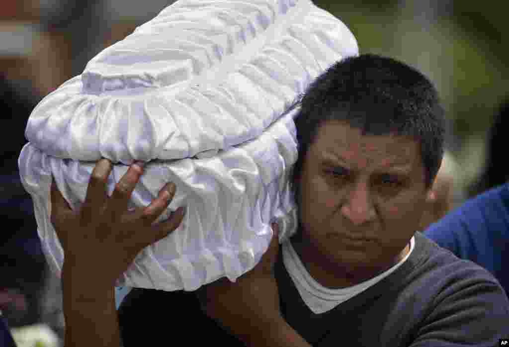 Welsar Nazario carries the coffin of his five-month-old nephew Alezandro Macario, who died in a mudslide, to the Santa Catarina Pinula cemetery on the outskirts of Guatemala City, Oct. 3, 2015. Rescue workers recovered more bodies after a hillside collapsed on homes on Oct. 1, while more are feared still buried in the rubble.