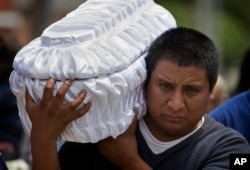 FILE - Welsar Nazario carries the coffin of his five-month-old nephew Alezandro Macario, who died in a mudslide, to the Santa Catarina Pinula cemetery on the outskirts of Guatemala City, Oct. 3, 2015.
