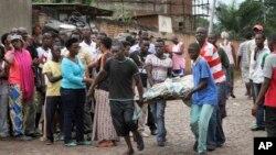 Warga mengangkut korban tewas bentrokan di Bujumbura, Burundi hari Sabtu (12/12).