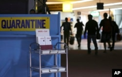 Passengers walk past the medical quarantine area showing information sheets on Middle East respiratory syndrome (MERS) at the arrivals section of Manila's International Airport in Paranaque, south of Manila, April 16, 2014.