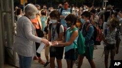Siswa yang memakai masker wajah untuk mencegah penyebaran virus corona mendisinfeksi tangan mereka sebelum masuk sekolah di Spanyol, Senin, 14 September 2020. (Foto: AP)