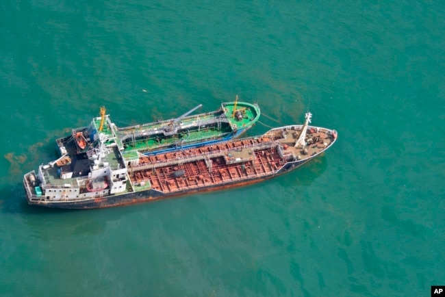 This May 24, 2018, photo released by Japan's Ministry of Defense shows the North Korean-flagged tanker Sam Jong 2, bottom, alongside the Myong Ryu 1, a vessel of unknown nationality, in the East China Sea. Japan's Foreign Ministry says a Japanese navy surveillance aircraft spotted a suspected unidentified ship apparently transferring fuel to a North Korean tanker in the open seas.