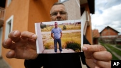 Bosnian Andjelko Djuric, 45, shows photos of his late brother Dragan Djuric, a police officer who was killed in Monday's attack at a police station in the eastern Bosnian town of Zvornik, 200 kilometers (124 miles) east of Sarajevo, April 28, 2015.