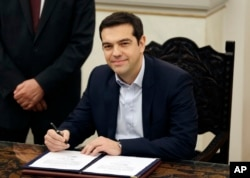 Greece's Prime Minister Alexis Tsipras poses for the photographers after taking a secular oath at the Presidential Palace in Athens, Jan. 26, 2015.