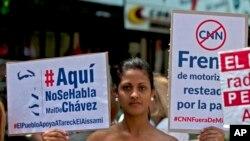 Partidarios del presidente venezolano, Nicolás Maduro, sostienen señales a favor de sus medidas durante una protesta frente a las oficinas del regulador de telecomunicaciones de Venezuela en Caracas.