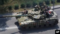 Separatis pro-Rusia mengendarai tank di jalanan kota Donetsk, Ukraina timur (10/8). Pertempuran masih terus berlanjut di Ukraina timur.