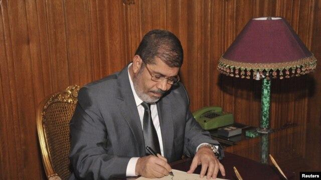 Misr prezidenti Muhammad Mursiy yangi konstitutsiyani kuchga kiritish haqida qaror imzolamoqda, 25-dekabr, 2012-yil