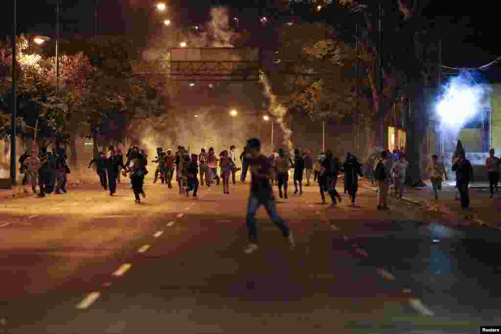 Anti-government demonstrators run from tear gas during clashes with riot police at Altamira Square in Caracas, Feb. 24, 2014.