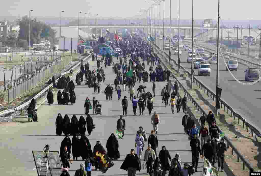 Iraqi Shi'ite Muslim pilgrims walk to the holy city of Karbala to mark Arbaeen in Baghdad's Doura district, Iraq, December 31, 2012.