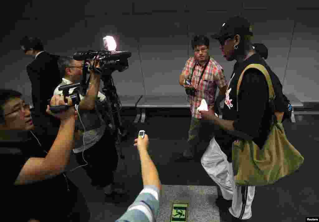 Former basketball star Dennis Rodman talks to media as he transits to Pyongyang from Beijing Capital International Airport, Sept. 3, 2013.