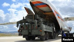 First parts of a Russian S-400 missile defense system are unloaded from a Russian plane at Murted Airport, known as Akinci Air Base, near Ankara, Turkey.