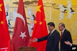FILE - Chinese President Xi Jinping, left, shows the way for Turkey's President Recep Tayyip Erdogan as they attend a signing ceremony at the Great Hall of the People in Beijing, July 29, 2015.