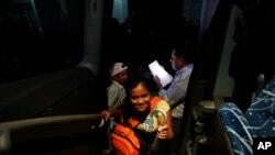 Los migrantes hondureños suben a un autobús al servicio del Instituto Nacional de Migración de México para regresar voluntariamente a su país de origen, en Huixtla, México. Foto de archivo.