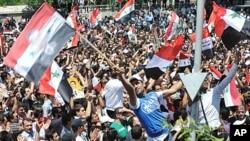 敘利亞總統阿薩德提議舉行全國性對話後﹐他的支持者在大馬士革街頭搖旗表示支持。
