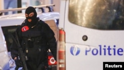 FILE - A Belgian special forces police officer patrols a street during a police raid in central Brussels, Belgium, Dec. 20, 2015. The ninth suspect arrested is believed to have been in contact via telephone with the cousin of the alleged organizer of the attacks.