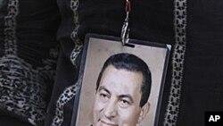 20일 호스니 무바라크 전 이집트 대통령이 입원한 병원 밖에서 그의 사진을 목에 걸고 서 있는 여성.