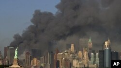 FILE - In this Sept. 11, 2001 file photo, thick smoke billows into the sky from the area behind the Statue of Liberty, lower left, where the World Trade Center towers stood.