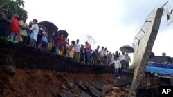 Regu penyelamat dan masyarakat sekitar berdiri di dekat tembok yang runtuh di Mumbai, India, 2 Juli 2019.