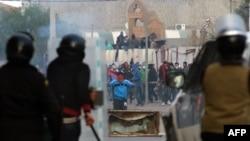Des policiers équipés du matériel anti-émeute font face à des manifestants à Kasserine, Tunisie, 21 janvier 2016.