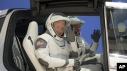 រូបឯកសារ៖ អ្នកអវកាសពីររូបចេញពីកន្លែងហាត់សម Neil A. Armstrong Operations and Checkout Building for Launch Complex 39A កាលពីថ្ងៃទី២៣ ខែឧសភា ឆ្នាំ២០២០។