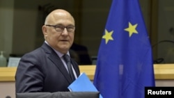 FILE - French Minister of Finance Michel Sapin arrives at the committee on economic and monetary affairs in Brussels, Belgium, May 7, 2015. Sapin is accused in a book of touching a journalist's underwear during the World Economic Forum gathering of the global business elite in 2015.