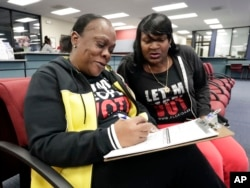 Former felon Yolanda Wilcox, left, fills out a voter registration form as her best friend Gale Buswell looks on at the Supervisor of Elections office, Jan. 8, 2019, in Orlando.