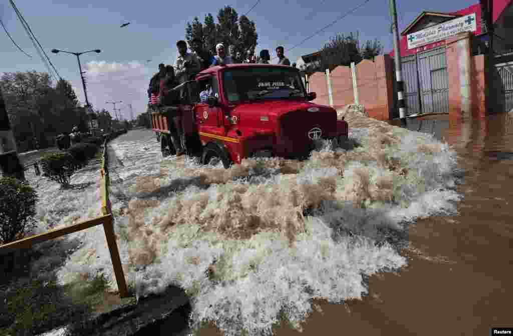 Xe cứu trợ nạn nhân lũ lụt người Kashmir chạy qua một con đường bị ngập lụt ở Srinagar, Ấn Độ.