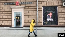 Seorang perempuan melewati toko pakaian tentara Rusia di seberang Kedutaan AS di Moskow, yang memasang poster Donald Trump pada hari pelantikannya menjadi Presiden ke-45 AS, 20 Januari 2016. (D. Schearf/VOA)