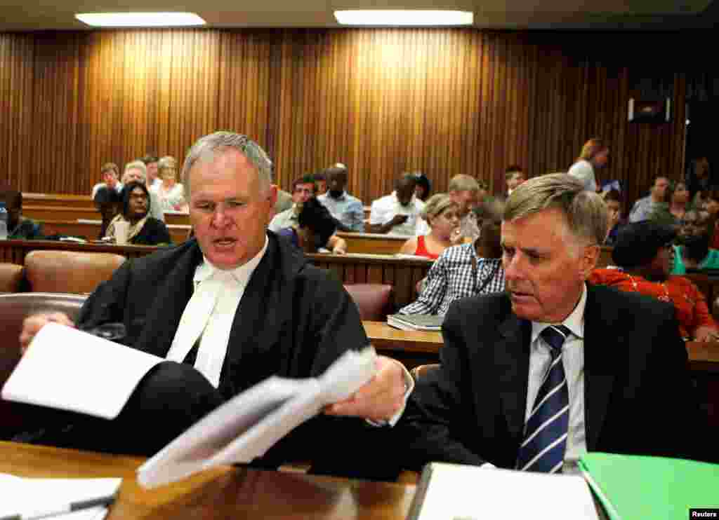 Oscar Pistorius's lawyers Barry Roux (L) and Brian Webber prepare documents before the start of the application to appeal some of his bail conditions at a Pretoria court, March 28, 2013.