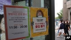 Pemberitahuan perubahan jam kerja dan kewaspadaan terhadap virus corona, kanan, terlihat di salah satu pintu gerbang toko kecantikan di Seoul, Korea Selatan, Jumat, 28 Agustus 2020. (Foto: AP)