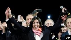 آن ایدالگو هنگام اعلام نتیجه انتخابات شهرداری پاریس. شهردار کنونی پاریس برتران دلانو پشت سر وی دیده می شود - پاریس، ۳۰ مارس ۲۰۱۴