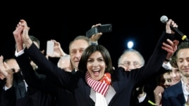 French Socialist Party deputy mayor of Paris, Anne Hidalgo, center, smiles, as outgoing mayor Bertrand Delanoe, stands behind her, during a speech after results were announced in the second round of the French municipal elections, in Paris, March 30, 2014.