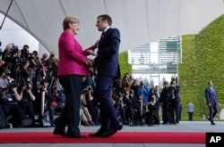 New French President Emmanuel Macron is welcomed by German Chancellor Angela Merkel in Berlin, May 15, 2017, during his first foreign trip after his inauguration the day before.
