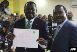 Kenya's National Super Alliance and opposition leader Raila Odinga (L) and running mate Kalonzo Musyoka show their clearance certificate, May 28, 2017 in Nairobi, after Odinga has presented his candidacy for the presidential race.