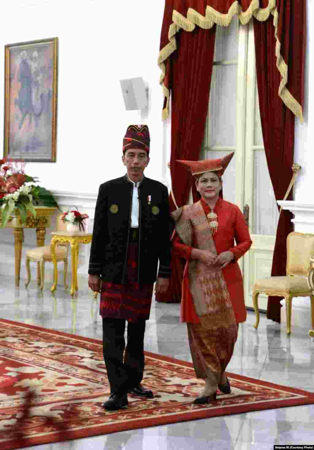 Presiden Jokowi yang mengenakan pakaian tradisional Tanah Bumbu Kalimantan Selatan, dan Ibu Negara Iriana mengenakan pakaian Minang Sumatera Barat, siap memimpin upacara bendera dan menyambut tamu di Istana Merdeka Jakarta, 17 Agustus 2017. (Courtesy: Setpres RI)