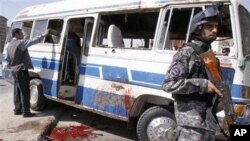 An Iraqi policeman stands guard near a destroyed bus at the site of a bombing in Basra, Iraq's second-largest city, 550 kilometers southeast of Baghdad, March 6, 2011