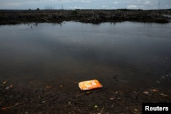 An empty bag of shrimp feed floats on the surface of a stream outside the Sunlight Seafood shrimp farm in Pitas, Sabah, Malaysia, July 6, 2018.