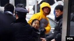 Seorang aktivis Hak Asasi Manusia Tiongkok diseret menjauhi wartawan dan para diplomat di luar gedung pengadilan tempat Ni Yulan dan suaminya, Don Jiqin akan diadili di Beijing (29/12).