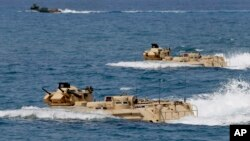 FILE - U.S. Navy amphibious assault vehicles with Philippine and U.S. troops on board are seen during joint exercises near a beach facing one of the contested islands in the South China Sea known as the Scarborough Shoal in the West Philippine Sea